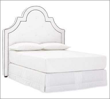 Tall white upholstered headboard with curves and arches from Pottery Barn