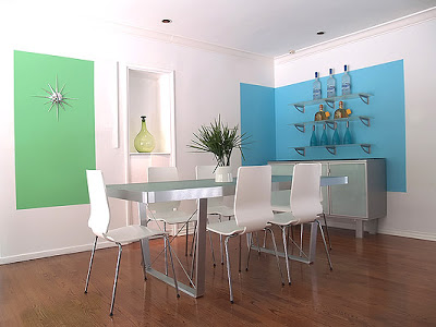 Bright modern dining room designed by Vanessa de Vargas with blue and green blocks of color on white walls, sleek white dining room chairs and a frosted glass and metal dining table and buffet