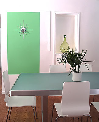 Close up of the green block with a sunburst wall decor painted on a white wall in a modern dining room designed by Vanessa de Vargas