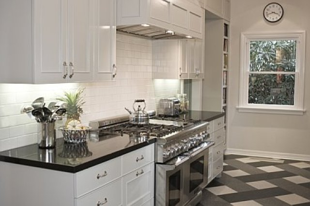 Kitchen after remodeling by Newman & Wolen Design with black quartz counter top, grey cabinets with molding detail, off white subway tile backsplash and a stainless gourmet range and oven