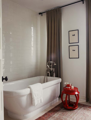 Master bathroom with floor to ceiling white subway tile wall, stand alone tub and a red lacquer stool