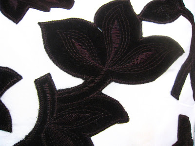 Detail of a brown and white floral pillow inspired by Madeline Weinrib