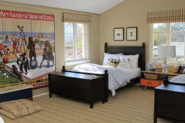 Kids bedroom with dark wood beds with trunks at the foot, a large circus poster and striped roman shades