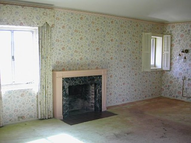 Master bedroom with floral wallpaper, old carpet and a fireplace before remodeling