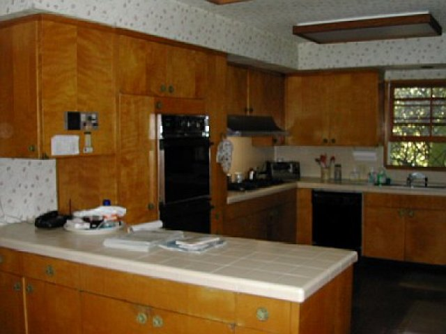 Kitchen before remodeling with honey colored wood cabinets and floral wallpaper