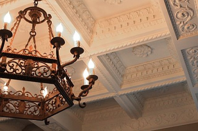 Original ornate coffered ceiling and a large Spanish iron chandelier in a living room after remodeling