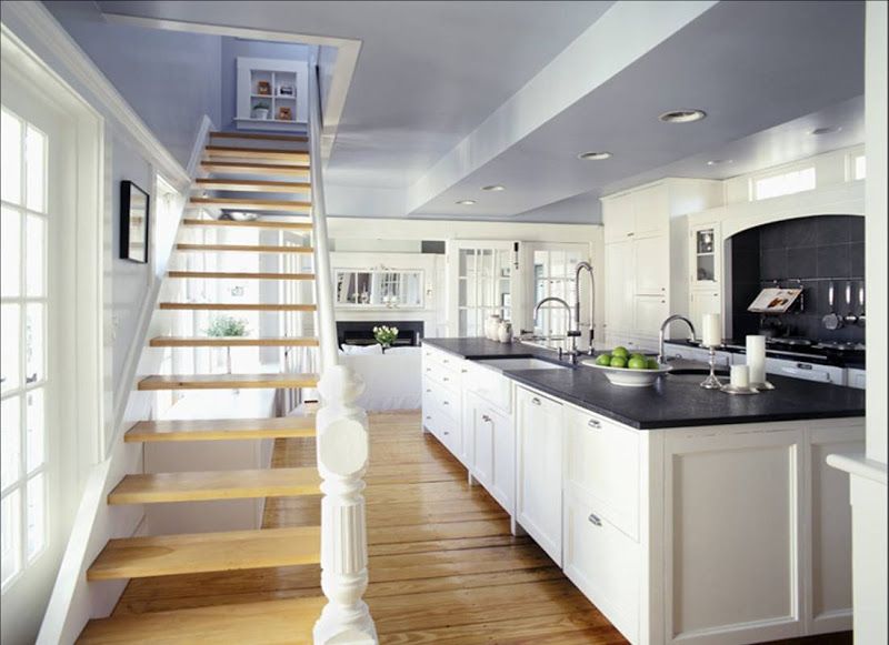 Open kitchen with dramatic staircase, wood floor, black granite counter top and dark slate tile backsplash