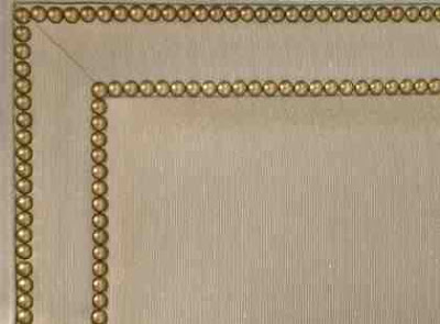Close up of gold nailhead double border trim on an upholstered bed from Jayson Home & Garden