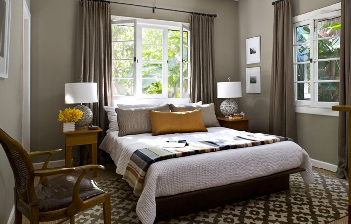 Bedroom with grey walls with white trim, taupe curtains, simple platform bed with white bedding and a stripe throw, a Moroccan rug and wood nightstands
