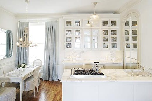 White kitchen by Kelly Giesen with white marble countertops, mirrored paned kitchen cabinets, a traditional dining table and chair and pale blue drapes
