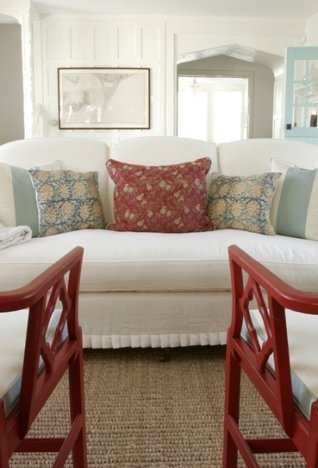 beach house living room with red Chippendale armchairs, a classic white sofa, and white paneled walls