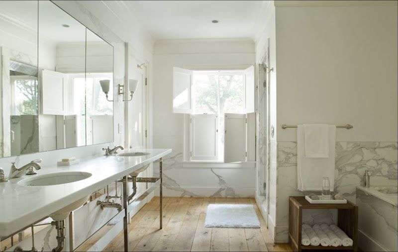 Spa like bathroom with white marble walls, unfinished wide plank wood floors and classic double sink