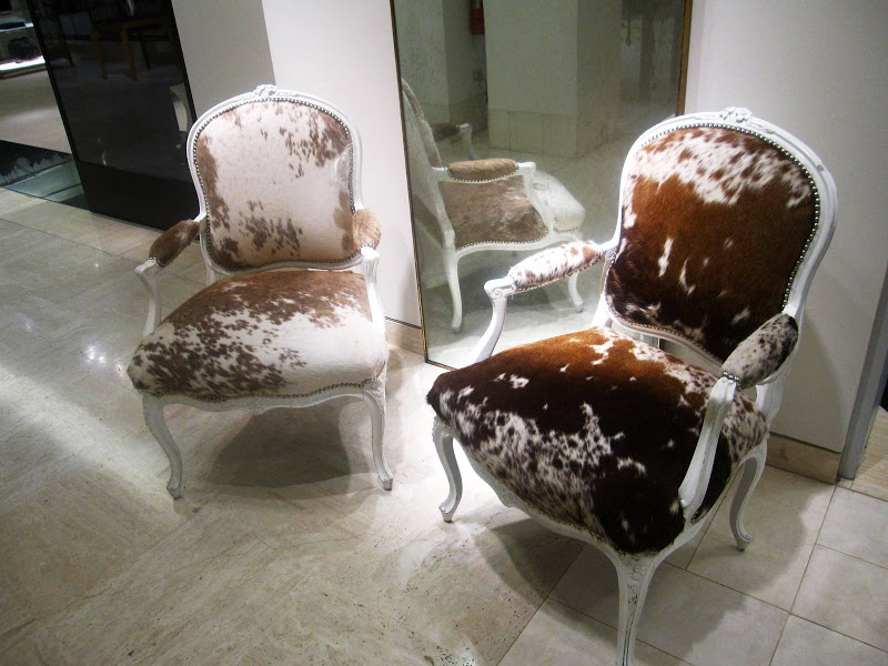 A pair of brown and white cow hide upholstered Louis XV bergeres with nailhead trim and glossy white lacquer paint in Neiman Marcus