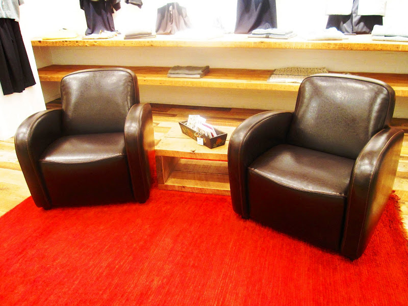 Two brown leather club chairs are set on a bright red rug in Neiman Marcus