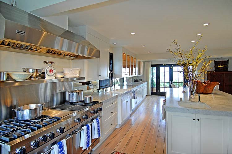 Long gourmet kitchen with wide plank natural stained wood floor, marble countertops, stainless appliances, white cabinets and drawers