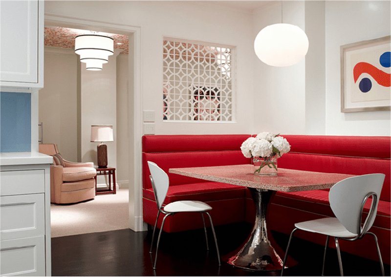 Breakfast nook with red leather corner banquette seating, a table with a chrome tulip inspired base with a square stone top and dark wood floor