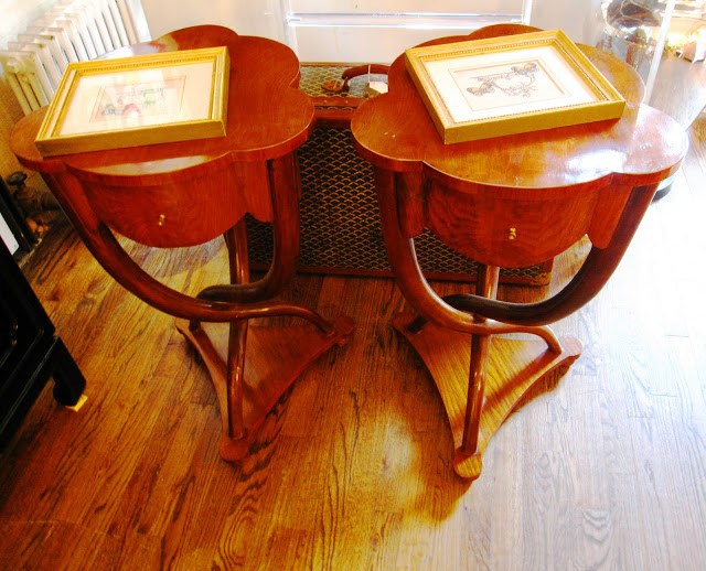 Two wooden scalloped side tables inside the Elizabeth Bauer store