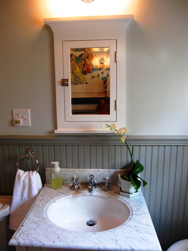 Bathroom by Newman & Wolen Design with grey wainscoting, white wood frame medicine cabinet and oval sink with marble countertop