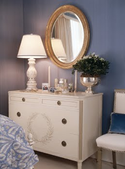 White dresser with a laurel wreath motif and a round gold mirror in a blue bedroom by Kelley Proxmire