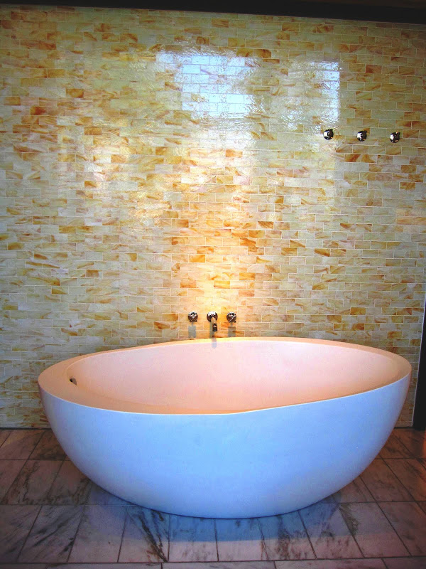 Bathroom with yellow marble mosaic subway tile wall, modern egg shaped freestanding tub and marble floor