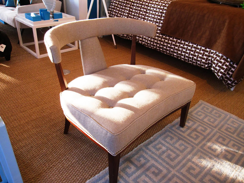 Extra wide upholstered chair with tufted seat, curved T-back and oak stained legs in the Jonathan Adler store