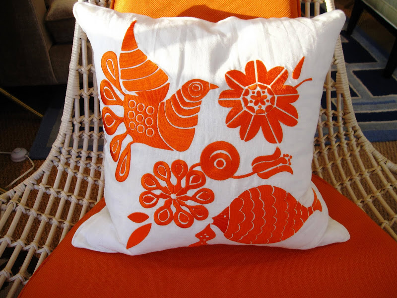 Orange and white embroidered pillow in the Jonathan Adler store