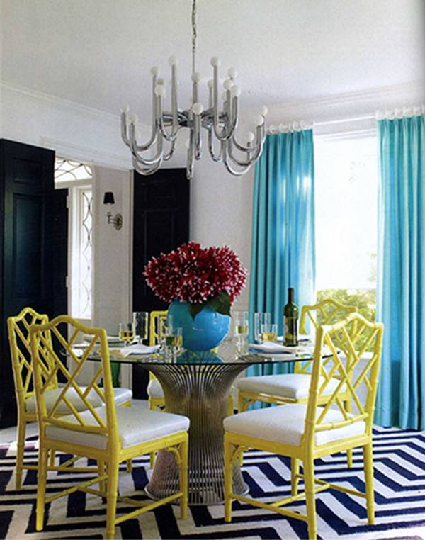 Dining room with mid-century modern Platner metal and glass dining table, turquoise curtains, a silver chandelier, yellow Chippendale chairs and a black and white chevron patterned rug