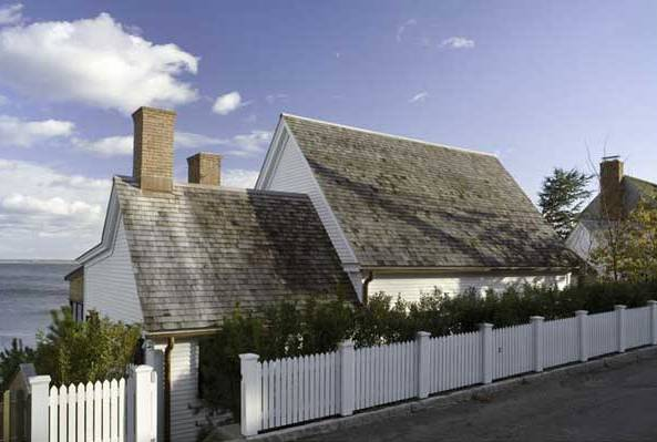 Exterior of a beach house by Stephan Jaklitsch with a white picket fence