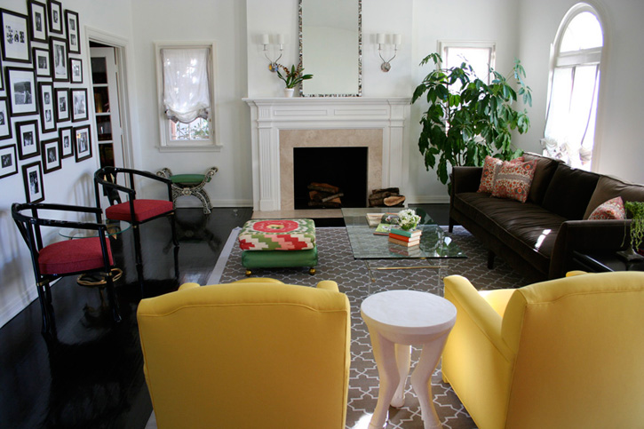 Hancock Park living room by M Design Interiors Inc. with dark wood floor, brown sofa, yellow armchairs, and a marble fireplace