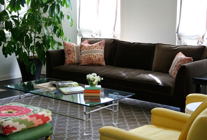 Hancock Park living room by M Design Interiors Inc. with a lucite table, yellow armchairs, colorful ottoman and a chocolate brown sofa