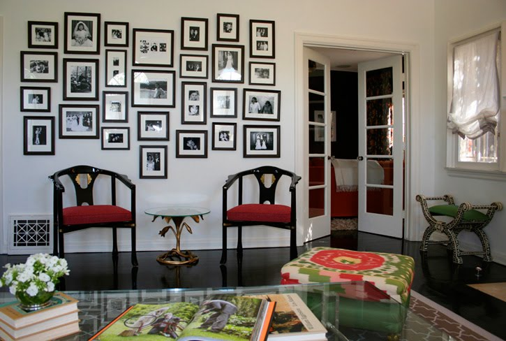 Hancock Park living room by M Design Interiors Inc. with black and white framed photos and two glossy black chairs with red seats