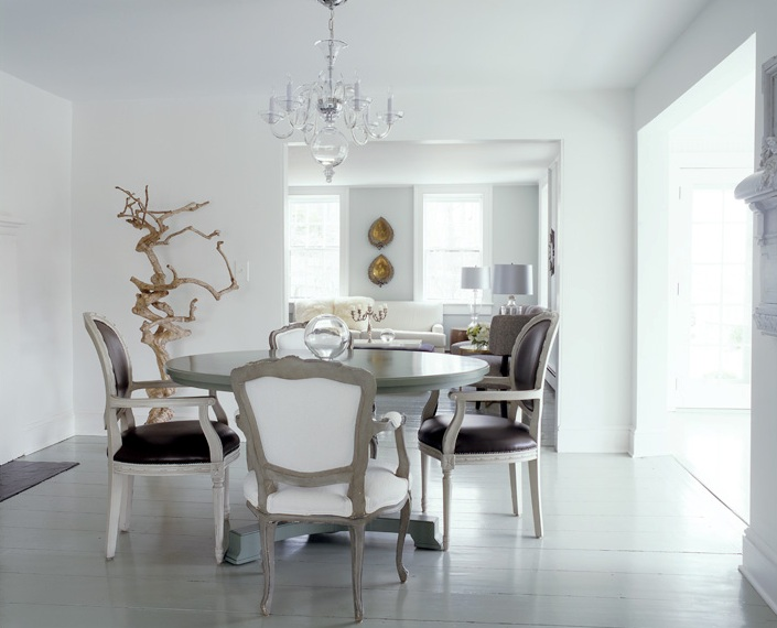 White dining room with driftwood sculpture, glass chandelier, round pedestal dining table and upholstered reproductions of Louis XVI chair