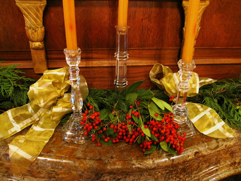 Fireplace in the library of a historic New Orleans mansion with a garland made of cedar boughs, red eucalyptus berries, crystal candle sticks and gold ribbon