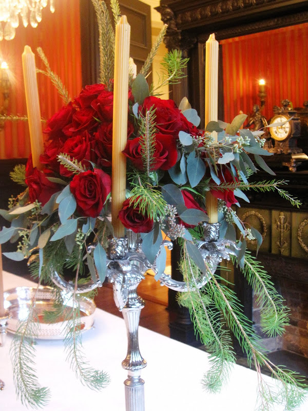 Flower arragement of red roses, pine sprigs and eucalyptus leaves in a grand silver candelabra in the formal dining room of a New Orleans mansion