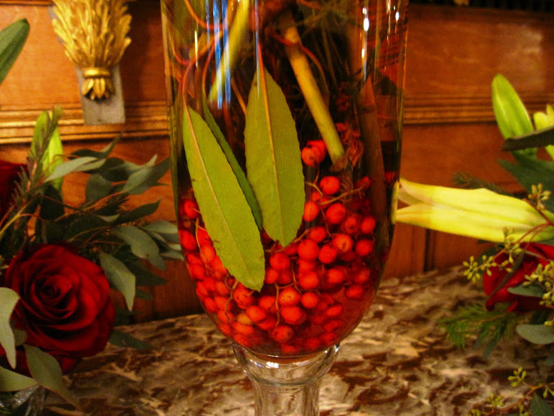 Close up of the base of a flower arrangement of white star gazer lilies, pine tree branches, eucalyptus leaves, red berries and a touch of red food coloring in the main entry hall in a New Orleans mansion