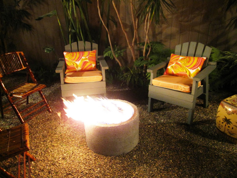 Cottage garden party with Adirondack chairs with pillows upholstered in pink, orange and yellow Trina Turk fabric, faux bamboo chairs and an outdoor firepit