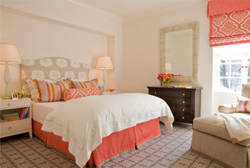 Bedroom by Massucco Warner Miller with coral roman shades, bead skirt and and accent pillows, grey graphic print carpet and a taupe and white headboard