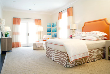 Bedroom by Massucco Warner Miller with an orange upholstered headboard, orange and cream striped curtains and a zebra print bedskirt