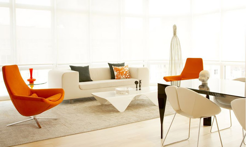 White living room with wrap around windows and modern orange chairs
