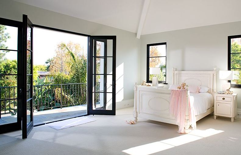 Bedroom in a Spanish Revival home with white bed frame and nightstand, black windows and glass door leading to a patio