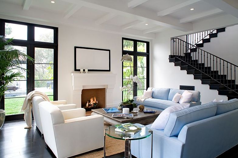 Living room in a Spanish revival home with light blue sofas, white armchairs, dark wood floor, black glass doors and a white fireplace