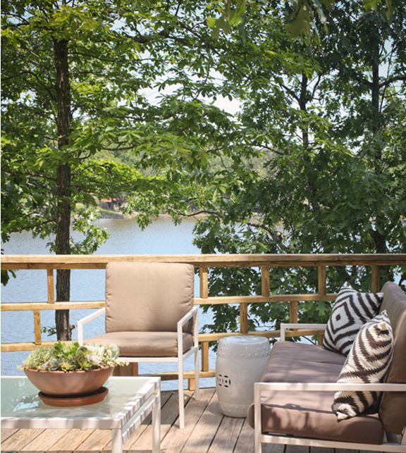 Outdoor patio with white iron furniture, diamond ikat style pillows, white ceramic garden stools and a lake view