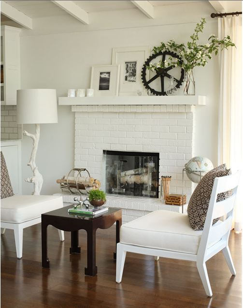 White painted brick fireplace flanked by two white lounge chairs in a living room