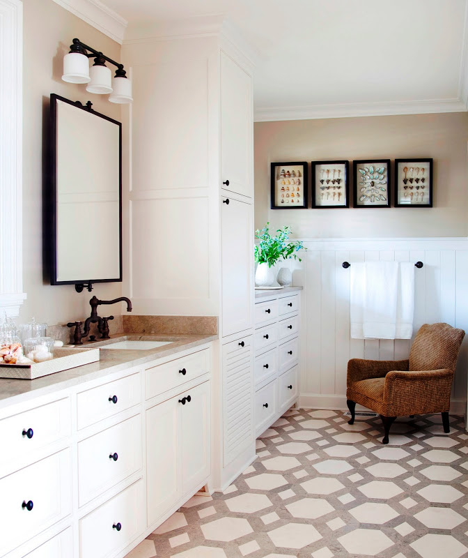 Traditional bathroom with hexagon tile floor, white drawers, beadboard walls and a brown armchair