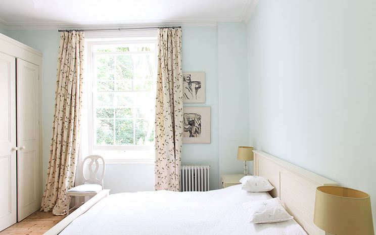 White bedroom in a London home with tall cabinets, fireplace, wide wood plank floor and leaf print curtains
