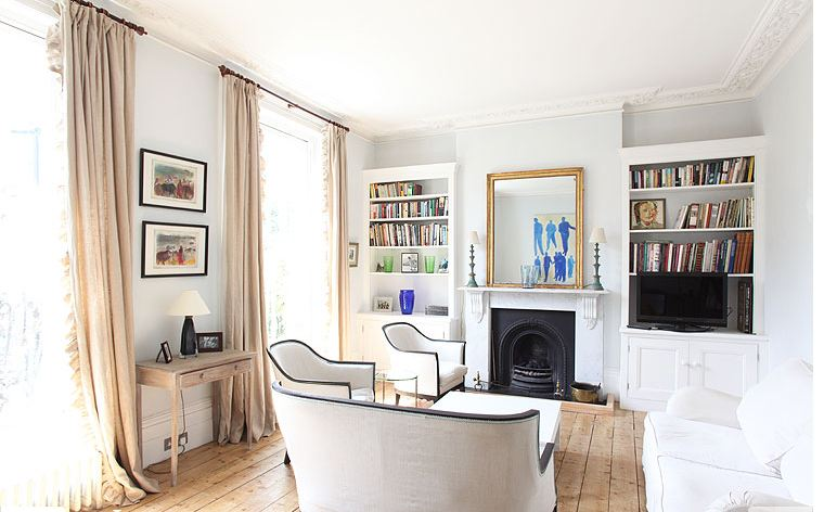 Living room in a London home with wide plank wood floors, tall windows, built-in bookshelves and an iron fireplace with white mantel