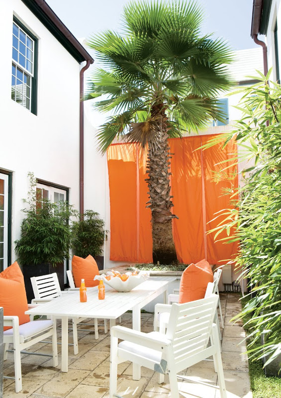 Orange parachute-like drapes hang behind a grand palm tree in the outdoor dining area of a Florida beach house