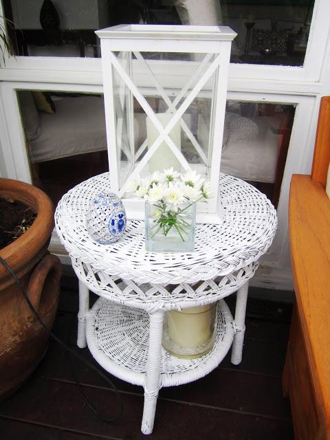 White hurricane lantern on wicker side table