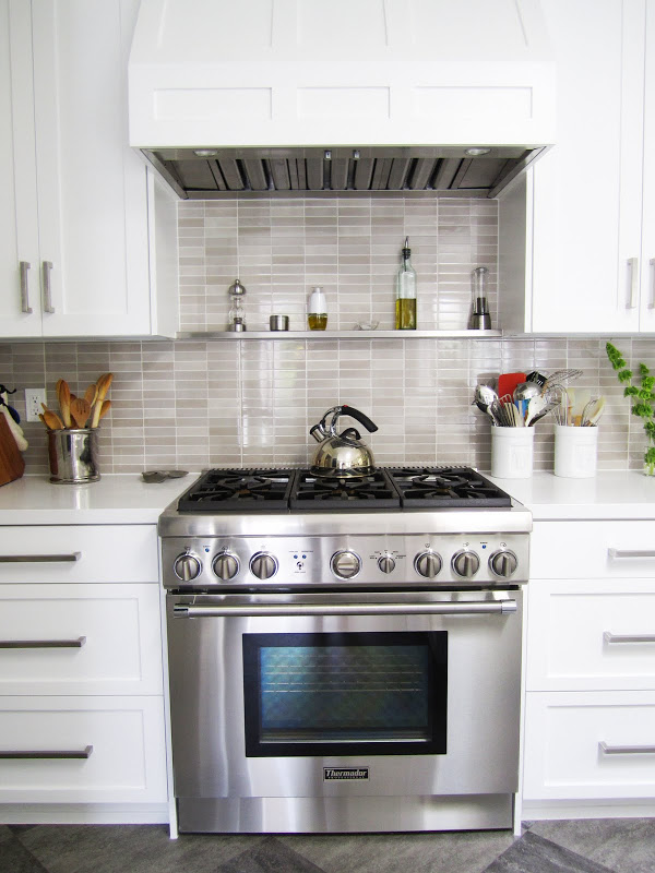 Gourmet kitchen with stainless steel Thermador oven, grey/brown backsplash and white paneled cabinets and hood