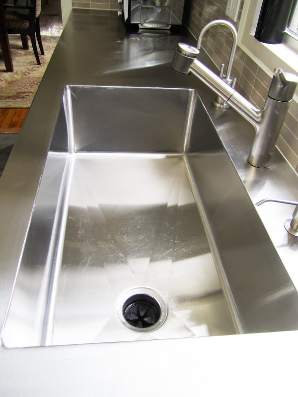 Kitchen with huge stainless steel sink fully integrated into the stainless counter.
